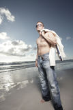 Image of a man on the beach. Young man in jeans and shirt removed on the beach Royalty Free Stock Photos