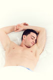 Image of man with both hands up on pillow sleeping in bed Royalty Free Stock Photography
