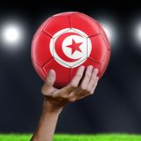 Man holding Soccer ball with Tunisian flag. Image of Man holding Soccer ball with Tunisian flag royalty free stock photography