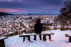 Winter Scene with Lone Man Sitting on Snowy Bench Overlooking City Center at Twilight stock photography
