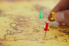 Image man& x27;s hand attached pins to a map, showing location or travel destination. selective focus. royalty free stock photo