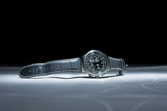 Image of a man's wristwatch with leather strap on the white table. Handwatch with leather strap on the table. Night photography Royalty Free Stock Image