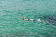 Man in a scuba mask swims in blue sea water. Image of man in a scuba mask swims in blue sea water Royalty Free Stock Photography