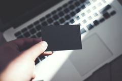Image Man Showing Blank Black Business Card and Using Modern Laptop Blurred Background. Mockup Ready for Private. Information. Sunlight Reflections Surface Stock Image