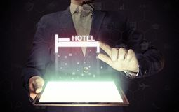 Man with a smartphone in his hands. Image of a man with a smartphone in his hands. He presses on the hotel icon. Search and online reservation of hotel Royalty Free Stock Image