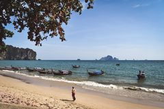 Man walking on the beach. Image of a man strolling along the shoreline of the Ao Nang Beach with longtail boats, a clear sky and islands in the background Stock Images