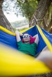 Image of man in sunglasses lying in hammock in forest stock photography