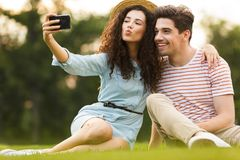 Image of man and woman 20s sitting on green grass in park and taking selfie on smartphone royalty free stock photography