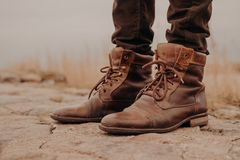 Image of mans legs in old boots. Concept of selling shoes. Autumn time. Horizontal view. Outdoor shot. Footwear stock photography
