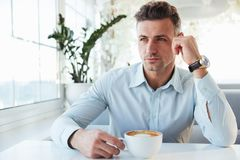 Image of masculine man 30s sitting alone in city cafe with cup o. F coffee beverage and looking aside with brooding sight Stock Photography