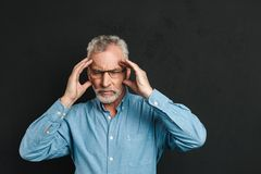 Image of mature man 60s with grey hair and beard suffering from. Migraine and rubbing temples due to headache isolated over black background Royalty Free Stock Image