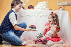 Image of merry cute boy treats sister sweets Royalty Free Stock Image