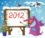 The image-message for winter holidays. Cute fire-spitting Dragon, writes on a forest board your message about celebration of Christmas and New Year Stock Photo