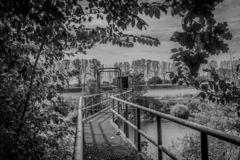 Image of a metal bridge with a closed gate forbidding passage in the middle of the vegetation. With a river in the background between Elsloo and Meers South royalty free stock photo