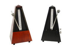 The image of metronomes. Under the white background Royalty Free Stock Images