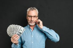 Image of middle aged rich man 60s with gray hair holding money f. An of 100 dollar bills and touching his grey mustache isolated over black background Stock Photos