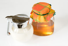Image of milk jug and can with honey. Hi-key image of milk jug and can with honey Royalty Free Stock Photo
