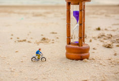 Image of mini figure dolls biker and sandglass on the beach Royalty Free Stock Photo