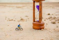 Image of mini figure dolls biker and sandglass on the beach Royalty Free Stock Photo