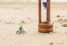 Image of mini figure dolls biker and sandglass on the beach Royalty Free Stock Image