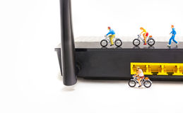 image of mini figure dolls riding bike and running on wifi route Royalty Free Stock Photos