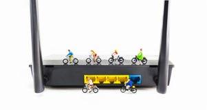 image of mini figure dolls riding bike on wifi router. Stock Photos