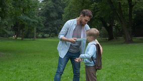 Image of a modern beard father giving a hi-five his little son in the park. Dad meets his son from elementary school. The end of the school day concept stock footage