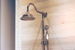 Image of a modern shower head splashing. Copper shower head, wood wall background. royalty free stock photos