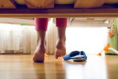 Image modifiée la tonalité de dessous le lit sur la jeune fille dans des pyjamas recherchant des pantoufles Photo stock