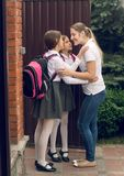 Image modifiée la tonalité de deux filles embrassant la mère avant de laisser à l'école Photo stock