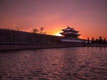 Image modifiée la tonalité de la forteresse avec une tour Cité interdite dans Pékin sur le fond du coucher du soleil au ciel clai Image libre de droits