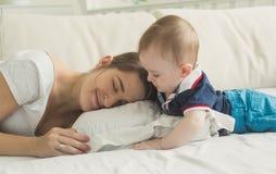 Image modifiée la tonalité de 10 mois de bébé garçon regardant la mère dormant dans le lit Photos stock