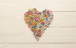 Image modifiée la tonalité des sucreries rondes colorées se situant dans la forme du coeur dessus Photographie stock