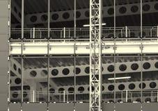 Image monochrome d'un grand chantier de construction avec le cadre en acier et des poutres avec les barrières et la grue de bâtim image libre de droits