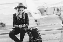 image monochrome La touriste de femme dans le chapeau s'assied à l'aéroport près de la fenêtre, utilise le smartphone Dans l'avio Images stock