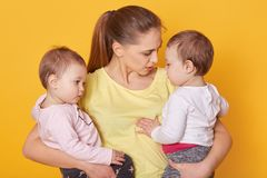 Image of mother with her sweet children, posing in studio. Mummy and girls twins, dressed casually, mom tells her doughters about. Mother`s Day. Little children royalty free stock photos