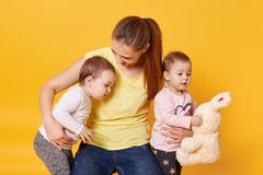 Image of mother with kids, playing with mommy while posing in photo studio, girl holds plushy rabbit, toddlers dressed in casual stock image