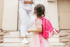 Image of mother standing on the stairs against the home saying goodbye to her daughter as she leave for kindergarten. Cute little. Girl wears dress and backpack royalty free stock photo