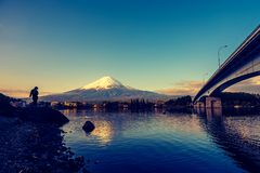 Image of Mountain Fuji and Lake Kawaguchi. Vintage tone image of Mountain Fuji and Lake Kawaguchi with Kawaguchiko Ohashi bridge.Silhouette shot people on stock images