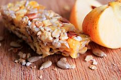 Muesli bar with nuts on the table. Image of muesli bar with and apple nuts on a table Stock Images