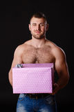Image of muscular man holding xmas gifts, isolated on black Royalty Free Stock Photography