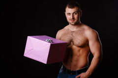Image of muscular man holding xmas gifts, isolated on black Stock Photo