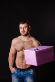 Image of muscular man holding xmas gifts, isolated on black Stock Image