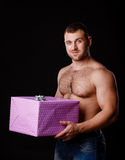 Image of muscular man holding xmas gifts, isolated on black Stock Photography