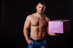 Image of muscular man holding xmas gifts, isolated on black Royalty Free Stock Photos