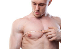 Image of muscular man measure his chest with measuring tape in centimeters. Isolated on white backgound. Image of muscular man measure his chest with measuring Royalty Free Stock Photography