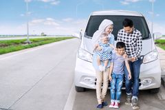 Muslim family using a tablet on the highway. Image of Muslim family leaning on the hood of their car while using a tablet. Shot on the highway stock photo