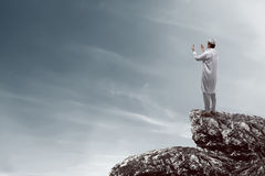 Image of muslim man standing on the top of cliff Stock Image