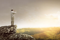Image of muslim man standing on the top of cliff Royalty Free Stock Images