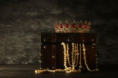 Image of mysterious opened old wooden treasure chest with light and queen/king crown with red Rubies stones. fantasy medieval peri. Od. Selective focus royalty free stock images